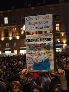 "Sign in front of the Capitole at the rally in support of the victims of the 2015 Charlie Hebdo shooting (""That's the Freedom of speech that has been murdered""). Below, the issue published that very morning. 7 January 2015. Source: Gyrostat (Wikimedia, CC-BY-SA 4.0)"